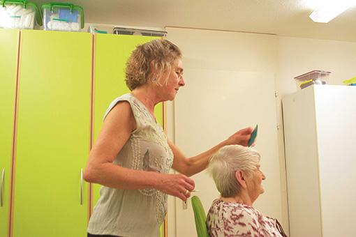 Eine stehende Frau frisiert eine sitzende Frau