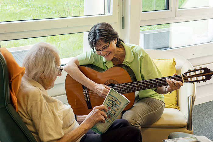 Betreuungsperson spielt Gitarre