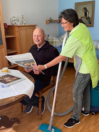 Frau mit Staubsauger stehend sowie Mann mit Zeitung sitzend